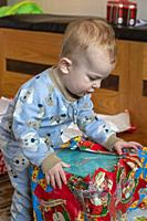 Denver, Colorado - Hendrix Hjermstad, a year and a half old, tears open a present on Christmas morning.