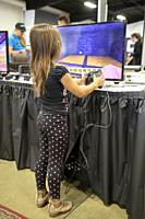 Still in diapers, a little girl tries computer gaming at a high tech exhibition in Costa Mesa, CA.