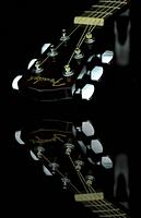 Close up image form a classic guitar on a mirror as background painted with light.