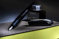 Calligraphy pen on a closed book and a can of ink.