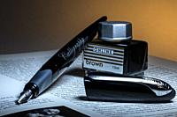 Calligraphy pen on a open book and a can of ink.