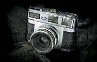 A vintage camera painted with lights on black coals as background.