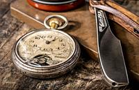 Men's cosmetics shaving razor and a vintage pocket watch on a wooden background.