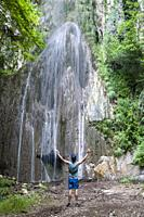 My waterfall, a man with outstretched arms seems to suggest in front of a waterfall in the Valle delle Ferriere, the Amalfi Coast, Italy.