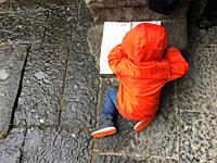 A young child wearing an orange poncho works on his sketch book barely inches away from the wet pavement, Naples, Italy.
