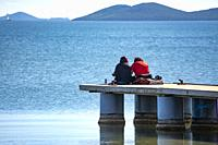 Couple sitting on the end of the jetty at Los Alcazares in Murcia Spain.