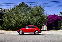 Historic red Volkswagen Bug parked in a residential neighborhood, California, USA