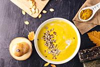 Homemade pumpkin soup with sunflower and sesame seeds on top, served in a white bowl, alongside curry, pumpkin seeds and spices on a dark surface. Ove...
