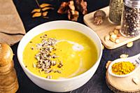 Close up of homemade pumpkin soup with sunflower and sesame seeds, coconut milk, nutmeg and yellow curry in a ceramic bowl.