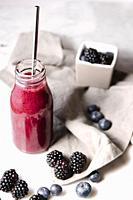 Pink vegan smoothie, berries and a metal straw on a marble surface. Vertical image.
