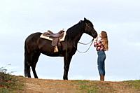Side view of a blonde teenager cowgirl in front of her black horse with the saddle.