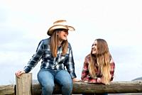 Young and teenager blonde cowgirls laughing on a wooden barrier.