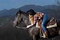 A blonde teenager girl hugging and lying on her black horse.