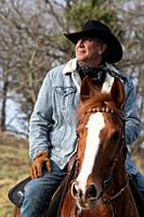 Close-up frame of a veteran cowboy man riding his arabian horse.