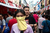 Singapore, Republic of Singapore, Asia - A woman covers her face with a mask at a street bazaar in Chinatown that takes place every year around the ti...
