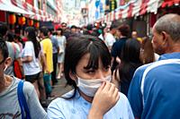 Singapore, Republic of Singapore, Asia - A woman covers her face with a surgical mask at a street bazaar in Chinatown that takes place every year arou...