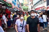 Singapore, Republic of Singapore, Asia - Pedestrians cover their faces with surgical masks at a street bazaar in Chinatown that takes place every year...