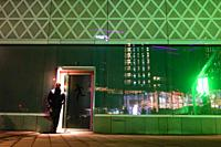 Stockholm, Sweden A person at night walks by a shiny green building in Solna.