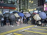 Hong Kong, Hong Kong SAR - August 3, 2019: a group of protesters building a makeshift barricade in Nathan Road during a rally.