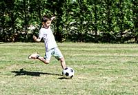 Child playing football in a stadium. Trees on the background.