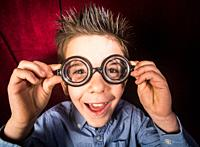 Smiled child with big glasses. Red curtain background.