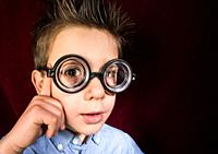 Thinking child with big glasses. Red curtain background.