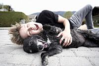 Teenager playing with his dog, in Gaissach, Bavaria, Germany.