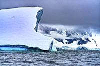 Floating Blue Iceberg Floating Sea Water Snow Mountains Glaciers Charlotte Bay Antarctic Peninsula Antarctica. Glacier ice blue because air squeezed o...