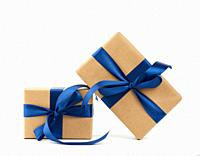 rectangle box wrapped in brown kraft paper and tied with a silk blue ribbon, gift isolated on a white background.