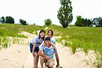 Father and daughers posing on dunes trail in Ludington, Michigan, USA. .