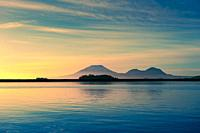 Kruzof Island and Mount Edgecumbe on a calm evening west of Sitka, Alaska, USA. Kruzof Island is an island in the Alexander Archipelago in southeaster...