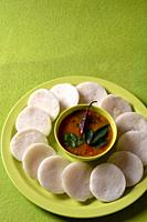 Idli with Sambar in bowl on green background, Indian Dish : south Indian favourite food rava idli or semolina idly or rava idly, served with sambar an...