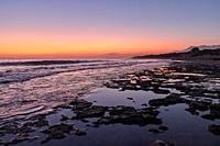 Beach rocks in low tide at the sunset in Marbella Cabopino beach, orange sky and blue water.