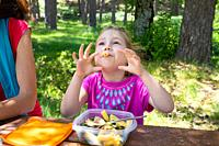 funny four years old blonde girl making fun playing with macaroni, eating pasta from a plastic lunchbox next to her mother in a table picnic in the co...