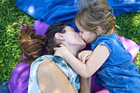 four years old blonde child kissing in mouth to woman mother, lying on blue and purple towels in the green grass of park.