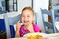 portrait of four years old blonde girl looking at and laughing, sitting in restaurant eating Spanish paella rice.