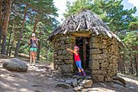 little daughter, five years old girl, pointing with finger, next to her mother, both mountaineers, in ancient hut in forest of Canencia mountain (Madr...