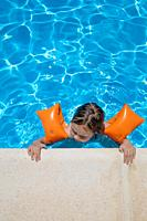aerial shot: four years old blonde child with orange floater sleeves in arms, armbands, clinging or holding on to the curb of the swimming pool, with ...