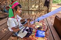 Kayan Lahwi woman with brass neck coils and traditional clothing spinning cotton in her shop. She has displayed behind her the hand woven fabric she s...