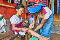 Kayan Lahwi woman putting a brass coil on the lower leg of her daughter. The Long Neck Kayan (also called Padaung in Burmese) are a sub-group of the K...