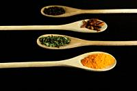 four wooden spoons placed symmetrically with saffron, oregano, chillies and black pepper on dark background.