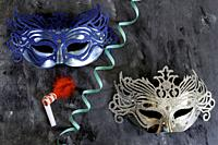 silvery and blue carnival masks with serpentine and matasuegras on dark background.