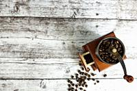 coffee grinder with coffee grains on wooden table from above. Top view.