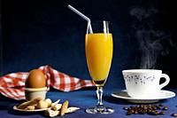 glass of orange juice with a straw, boiled egg in an egg cup with bread, steaming cup of coffee, coffee grains and napkin on blue fantasy background.