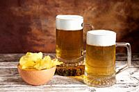 two beer mugs with foam and bowl of chips on wood table and brown fantasy background.