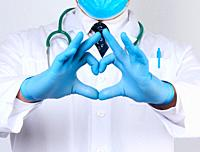 adult doctor man in a white medical coat with a stethoscope on his neck shows a heart gesture with his hands, wearing blue gloves on his hands, white ...