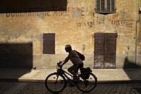 Silhouette riding bicycle down street in french Mediterranean fishing port of Cassis, France,.