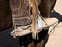 Close up detail of a cowboy's boot in a saddle stirrup with leather chaps and fringe. The leather chaps protect the cowboy's legs from thorny brush. R...