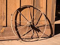 An old rusty metal rim from a wagon wheel leans against the wall of the tack barn on a ranch near Moab, Utah.