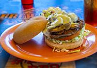 Hamburger sandwich with bun, mushrooms, cheese, lettuce and tomato on orange plate againist a blue background.